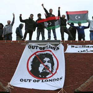 Protesters shout from the rooftop after taking over a house thought to belong to Saif al-Islam Gaddafi