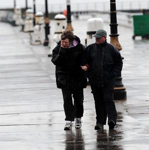Two people brave the elements on the promenade at Whitby, North Yorkshire