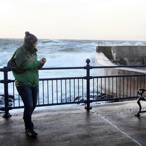 A woman watches waves breaking over the harbour wall at Portstewart, Co Londonderry