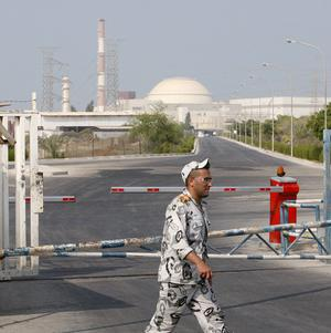 A security guard walks past a gate of the Bushehr nuclear power plant in Iran (AP)
