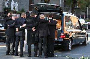 Ronan Keating, Mikey Graham, Shane Lynch and Keith Duffy look on as  the coffin is loaded into the hearse after the funeral of Boyzone singer Stephen Gately at St Laurence O'Toole Church in Dublin
