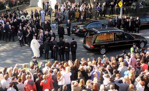 Boyzone members  and family gather round the hearse carrying the coffin of Stephen Gately outside St Laurence O'Toole Church in Dublin