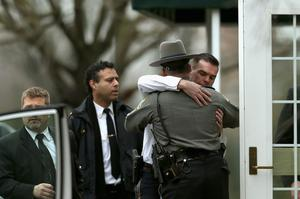 FAIRFIELD, CT - DECEMBER 17:   Two law enforcement officers embrace as they arrive for the funeral services of six year-old Noah Pozner, who was  killed in the shooting massacre in Newtown, CT, at Abraham L. Green and Son Funeral Home on December 17, 2012 in Fairfield, Connecticut. Today is the first day of funerals for some of the twenty children and seven adults who were killed by 20-year-old Adam Lanza on December 14, 2012.  (Photo by Spencer Platt/Getty Images)