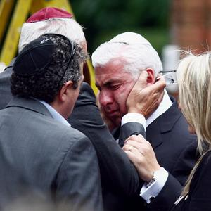 The father of Amy Winehouse, Mitch, is consoled outside Golders Green Crematorium
