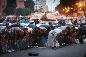 CAIRO, EGYPT - JANUARY 30:  People pray in front of army tanks in Tahrir Square on January 30, 2011 in Cairo, Egypt. Cairo remained in a state of flux and marchers continued to protest in the streets and defy curfew, demanding the resignation of Egyptian president Hosni Mubarek. As President Mubarak struggles to regain control after five days of protests he has appointed Omar Suleiman as vice-president. The present death toll stands at 100 and up to 2,000 people are thought to have been injured during the clashes which started last Tuesday. Overnight it was reported that thousands of inmates from the Wadi Naturn prison had escaped and that Egyptians were forming vigilante groups in order to protect their homes.   (Photo by Peter Macdiarmid/Getty Images) *** BESTPIX ***