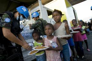 In this photo provided by MINUSTAH, Bolivian UN peacekeepers distribute water and meals to the residents in Cite Soleil