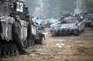 ISRAEL/GAZA BORDER, ISRAEL - NOVEMBER 19:  (ISRAEL OUT) An Israeli soldier stands near tanks in a deployment area on November 19, 2012 on Israel's border with the Gaza Strip. The death toll has risen to at least 85 killed in the air strikes, according to hospital officials, on day six since the launch of operation 'Pillar of Defence.'  (Photo by Lior Mizrahi/Getty Images)