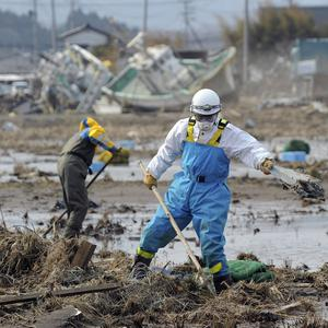 Japanese police officers search for missing residents following the March 11 tsunami, triggered by a massive earthquake (AP)