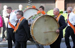 Robert Russell (right) beats out a steady rythm on the Lambeg drum during the glorious Twelfth parade through Lurgan. RicPics. 12/7/12.