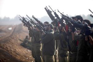 Israeli soldiers prepare weapons in a deployment area on November 19, 2012 on Israel's border with the Gaza Strip