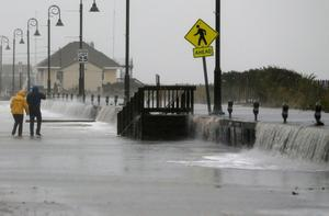 CAPE MAY, NJ - OCTOBER 29: People walk across Beach Ave. as flood waters from Hurricane Sandy rush in on October 29, 2012 in Cape May, New Jersey. Later today the full force of Hurricane Sandy is expected to hit the New Jersey coastline bringing heavy winds and floodwaters.  (Photo by Mark Wilson/Getty Images)