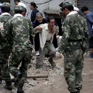 A man carries a woman across floodwaters after a mudslide swept into the town of Zhouqu, China