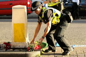 A female police officer places a floral tribute at the scene of a murder caused by gunman Derrick Bird on June 2, 2010 in Whitehaven, England