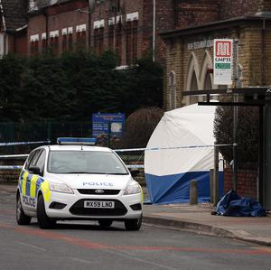 A police car parked close to a forensic tent in Old Trafford where an 18-year-old was stabbed to death
