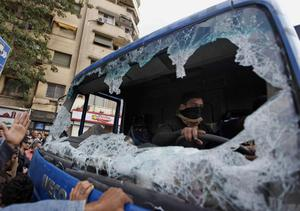 A protester sits in a police truck destroyed during clashes in Tahrir Square in Cairo, Egypt, Saturday, Nov. 19, 2011. Thousands of police clashed with protesters for control of downtown Cairo's Tahrir Square on Saturday after security forces tried to stop activists from staging a long-term sit-in there. The violence took place just nine days before Egypt's first elections since the ouster of longtime President Hosni Mubarak in February. (AP Photo/Khalil Hamra)