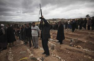 A Libyan man shoots his gun in the air during the funeral of Mohammed Idris in the eastern town of Beyda, Libya, Monday, Feb. 28, 2011. Idris was shot during the fighting with the Libyan military last week and died Sunday in the hospital. (AP Photo/Tara Todras-Whitehill)