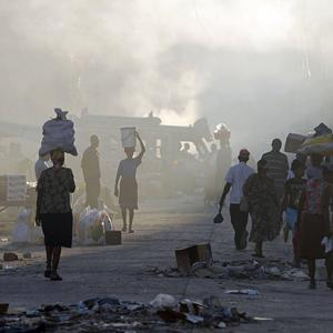 People walk through smoke coming from burning rubbish in downtown Port-au-Prince, Haiti (AP)