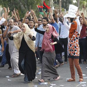 Demonstrators shout after militiamen acting as police fire in the air in an attempt to disperse their protest in front of Libya's parliament (AP/Paul Schemm)