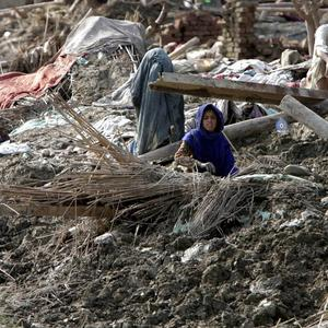 Pakistani flood affected victims sit in the rubble of their house in Aza Kheil near Peshawar (AP)