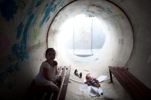 NITZAN, ISRAEL - NOVEMBER 19:  (ISRAEL OUT)  An Israeli girl takes cover in a large concrete pipe used as a bomb shelter during a rocket attack from the Gaza Strip on November 19, 2012 in Nitzan, Israel. According to reports November 19, 2012, at least 90 Palestinians have been killed and more than 700 wounded during the Israeli offensive in the Gaza Strip.  (Photo by Uriel Sinai/Getty Images)