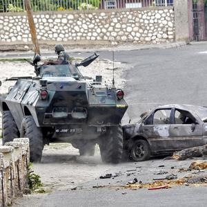 Jamaica Defence Force troops enter a barricaded street in Hannah Town, West Kingston