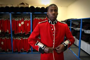 WINDSOR, ENGLAND - APRIL 21:  Irish Guardsman Bortnill St'Ange tries on his ceremonial uniform in the store room at Victoria Barracks on April 21, 2011 in Windsor, England. The Irish Guards returned from active duty in Afghanistan at the beginning of April, and are now preparing for ceremonial duties. Prince William is the Colonel of the Regiment and the Irish Guards will be on duty at the Royal Wedding on April 29, 2011.  (Photo by Peter Macdiarmid/Getty Images) *** Local Caption *** Bortnill St'Ange;