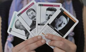 "A woman holds up cards featuring  Mao Zedong, Josef Stalin, Nicolae Ceausescu and Adolf Hitler from the ""Das Fuehrer Quartett"" (Tyrant Quartet) card game at a Berlin shop on July 17, 2008."