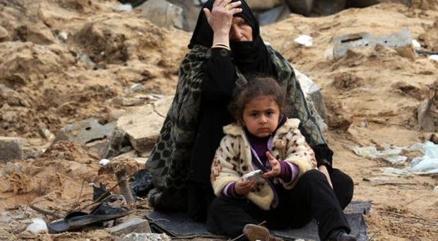 A mother and child sit among the ruins of their home in Rafah, southern Gaza, one of 4,000 homes destroyed in the war
