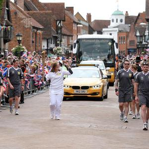 Camilla Hadland carries the Olympic Flame on the Torch Relay leg through the streets of Stratford-Upon-Avon