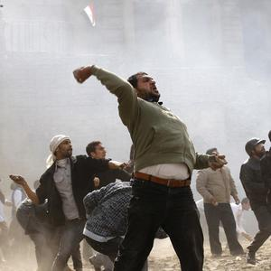 Anti-government protesters throw stones during clashes in Cairo (AP)