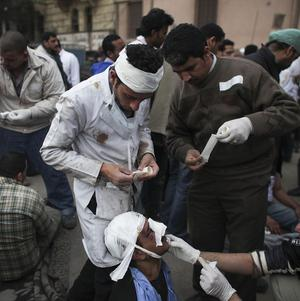 An injured Egyptian doctor treats a suspected supporter of president Hosni Mubarak near Tahrir Square in Cairo (AP)