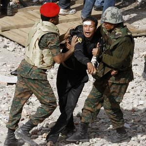 Egyptian soldiers restrain a pro-government protester amid violent clashes (AP)