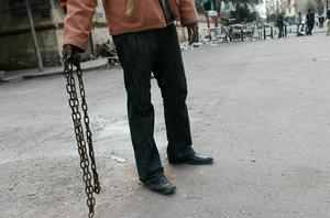 CAIRO, EGYPT - JANUARY 30:  An Egyptian man holds a chain as part of a ad-hoc neighborhood security militia in residential neighborhood in central Cairo the afternoon of January 30, 2011 in Cairo, Egypt. Cairo remained in a state of flux and marchers continued to protest in the streets and defy curfew, demanding the resignation of Egyptian president Hosni Mubarek. As President Mubarak struggles to regain control after five days of protests he has appointed Omar Suleiman as vice-president. The present death toll stands at 100 and up to 2,000 people are thought to have been injured during the clashes which started last Tuesday. Overnight it was reported that thousands of inmates from the Wadi Naturn prison had escaped and that Egyptians were forming vigilante groups in order to protect their homes.   (Photo by Chris Hondros/Getty Images)
