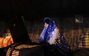 A Bahraini anti-government demonstrator works on her laptop in a tent camping out in protest at the Pearl roundabout in Manama, Bahrain, early Thursday morning, Feb. 17, 2011. (AP Photo/Hassan Ammar)