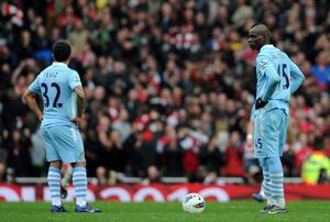 LONDON, ENGLAND - APRIL 08:  Carlos Tecez and Mario Balotelli of Man City stand dejected after Mikel Arteta of Arsenal scored a goal during the Barclays Premier League match between Arsenal and Manchester City at Emirates Stadium on April 8, 2012 in London, England.  (Photo by Michael Regan/Getty Images)