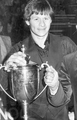 Alex Higgins.  Snooker Legend.  Alex Higgins, pictured with the championship trophy he intends to hold on to.  (12/03/1983)