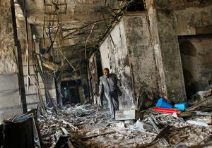 CAIRO, EGYPT - JANUARY 30:  A man walks through the charred remains of a burned government building January 30, 2011 in Cairo, Egypt. As President Mubarak struggles to regain control after five days of protests he has appointed Omar Suleiman as vice-president. The present death toll stands at 100 and up to 2,000 people are thought to have been injured during the clashes which started last Tuesday. Overnight it was reported that thousands of inmates from the Wadi Naturn prison had escaped and that Egyptians were forming vigilante groups in order to protect their homes after Police were nowhere to be seen on the streets.  (Photo by Chris Hondros/Getty Images)