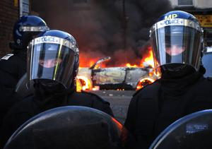 LONDON, ENGLAND - AUGUST 08:  Police officers in riot gear stand near a burning car in Hackney on August 8, 2011 in London, England. Pockets of rioting and looting continues to take place in various boroughs of London this evening, as well as in Birmingham, prompted by the initial rioting in Tottenham and then in Brixton on Sunday night. It has been announced that the Prime Minister David Cameron and his family are due to return home from their summer holiday in Tuscany, Italy to respond to the rioting. Disturbances broke out late on Saturday night in Tottenham and the surrounding area after the killing of Mark Duggan, 29 and a father-of-four, by armed police in an attempted arrest on August 4.  (Photo by Peter Macdiarmid/Getty Images)
