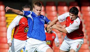 Peter Thompson is kept under close check by Cliftonville defender Peter Hutton as the Linfield striker's goal famine continued on Saturday