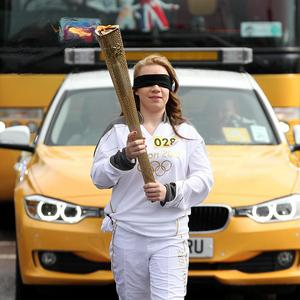 Mia Rathband, daughter of Pc David Rathband, carrying the Olympic Flame whilst blindfolded
