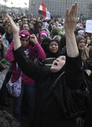 Women react during a demonstration in Cairo, Sunday, Jan. 30, 2011. The Arab world's most populous nation appeared to be swiftly moving closer to a point at which it either dissolves into widespread chaos or the military expands its presence and control of the streets. (AP Photo/Ahmed Ali)