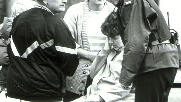 Harry Ward was shot dead in The Diamond Jubilee Bar, Shankill Road, Belfast October 1991. Pictured is his sister Sadie, being led away from the scene.