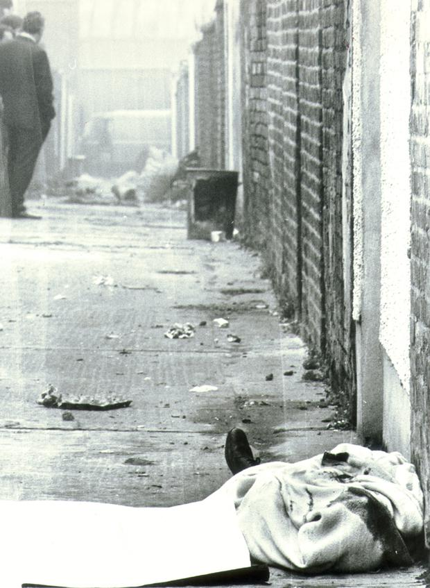 The body of Joseph Donegan, discovered  in an entry off Battenberg Street in Belfast's Shankill Road area, lies covered by a blanket.  25/10/1982.