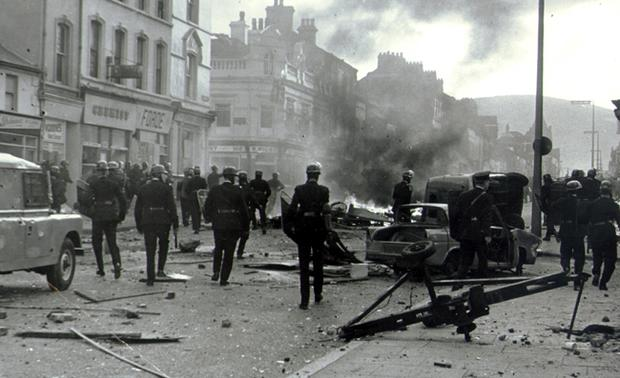 Steel helmeted police at a burning barricade across Shankill Road, Belfast, littered with stones and debris after a spree of rioting. 1969