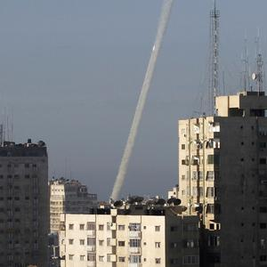 Rockets fired by Palestinian militants at southern Israel leave a thin trail of white smoke, seen between buildings in Gaza City.(AP)