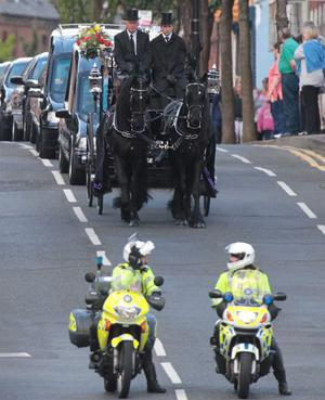 The funeral cortege of snooker legend Alex Higgins makes its way down the Donegall Road in south Belfast.  August 2010