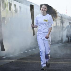 Helana Scott, number 15, carries the torch at the Great Central Railway station in Leicester