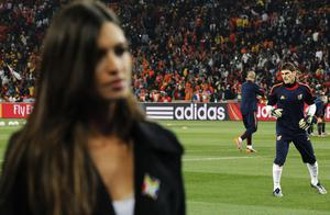 Spain goalkeeper Iker Casillas, right, warms up as his girlfriend, Spanish television broadcast journalist Sara Carbonero, foreground left, works from the sidelines before the World Cup final soccer match between the Netherlands and Spain at Soccer City in Johannesburg, South Africa