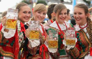 MUNICH, GERMANY - SEPTEMBER 23:  Polish girls, dressed with traditional Polish costume enjoy drinking beer after participating in the opening parade during day 2 of Oktoberfest beer festival on September 22, 2012 in Munich, Germany.This year's edition of the world's biggest beer festival Oktoberfest will run until October 7, 2012.  (Photo by Johannes Simon/Getty Images)
