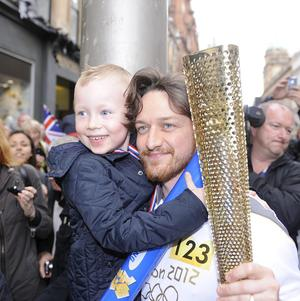 James McAvoy carrying the Olympic Flame on the torch relay leg in Glasgow (Ben Birchall/LOCOG/PA)
